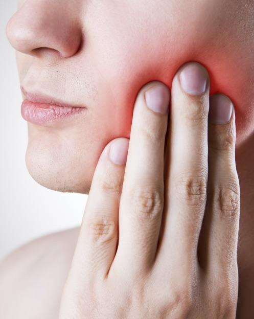 dentista portogruaro: mano che tocca guancia dolente