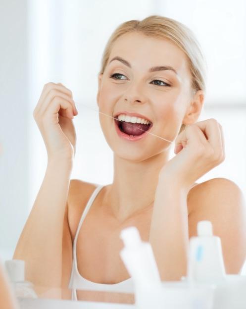 dentista portogruaro: giovane donna che si passa filo interdentale