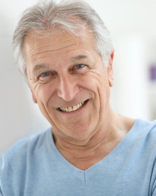 dentista portogruaro: signore con capelli bianchi e maglia azzurra che sorride